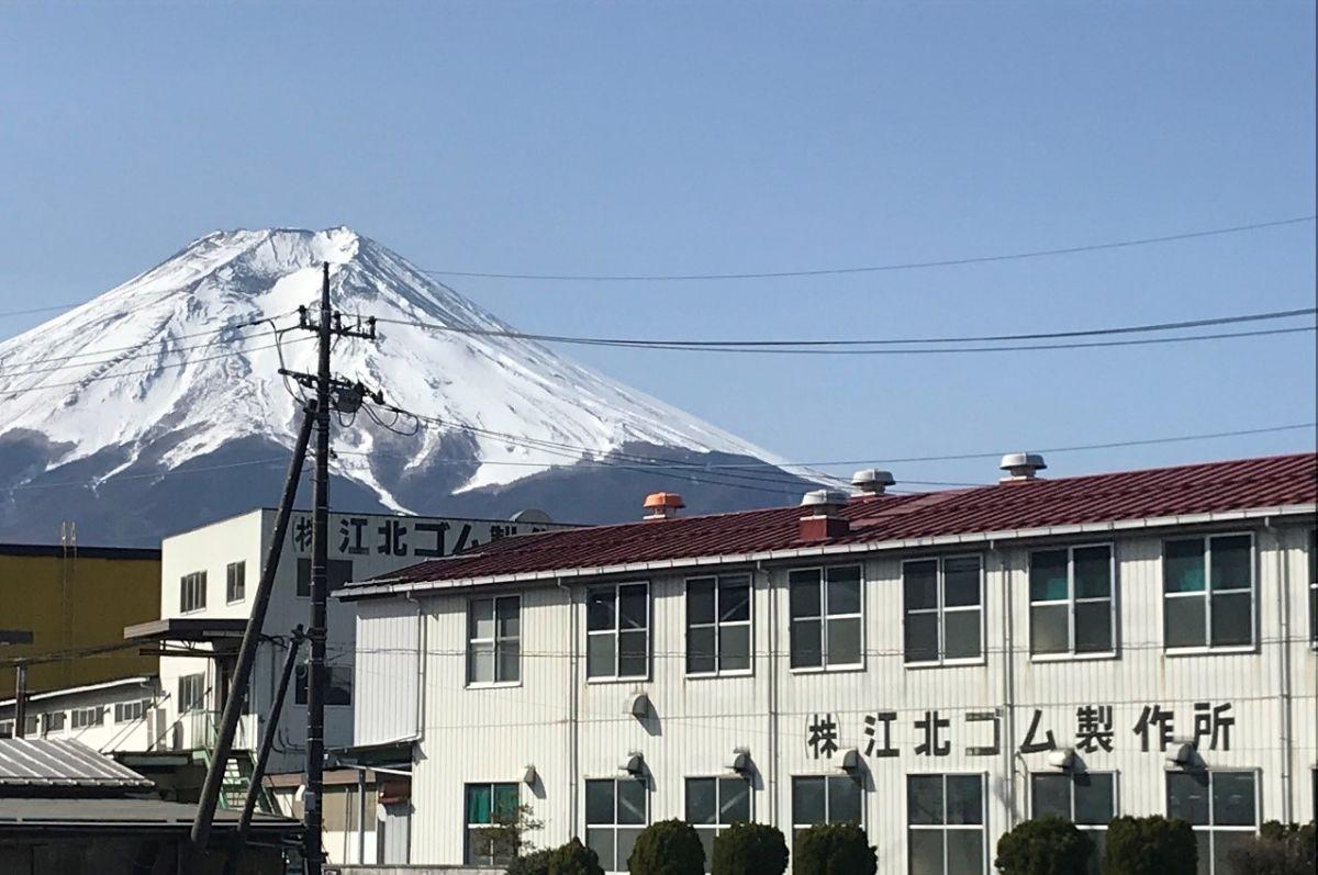 早春の陽光に輝く富士と株式会社江北ゴム製作所富士工場